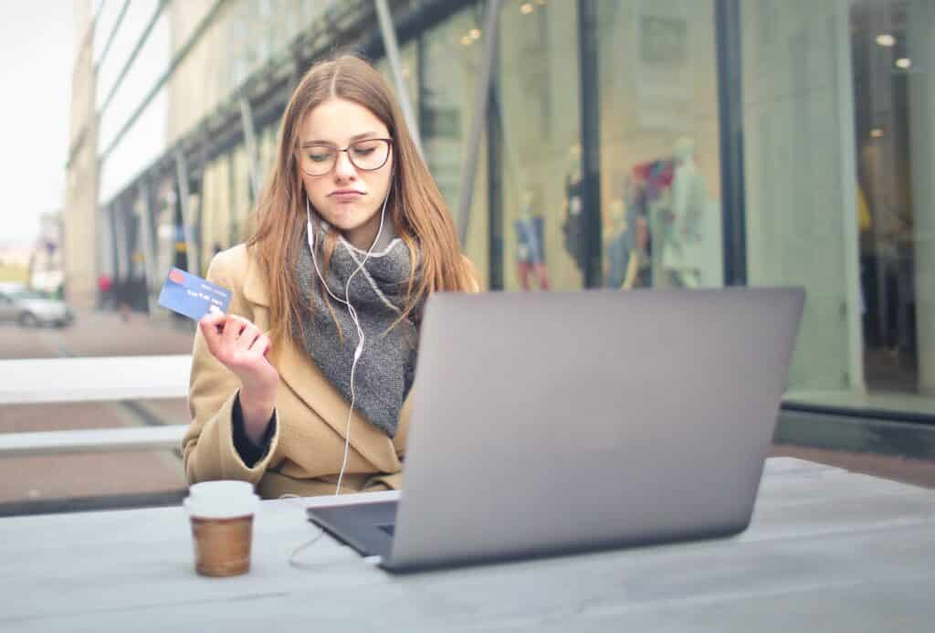 Woman with credit card making online purchase on laptop